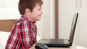 Enfant heureux skyping par l'intermédiaire de l'ordinateur portable, enfant de sourire à la maison, petit garçon observant les ba banque de vidéos