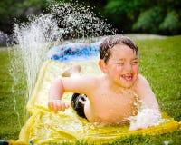Enfant heureux sur la glissière d'eau image libre de droits
