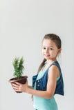 Enfant heureux sur le fond blanc avec le pot de l'usine Photographie stock