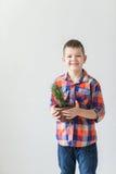 Enfant heureux sur le fond blanc avec le pot de l'usine Image stock