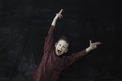 Enfant heureux sur le fond de tableau noir photo stock