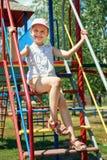 Enfant heureux sur le terrain de jeu extérieur, jeu en parc de ville, saison d'été, lumière du soleil lumineuse Image stock