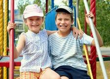 Enfant heureux sur le terrain de jeu extérieur, jeu en parc de ville, saison d'été, lumière du soleil lumineuse Photographie stock