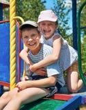 Enfant heureux sur le terrain de jeu extérieur, jeu en parc de ville, saison d'été, lumière du soleil lumineuse Image libre de droits