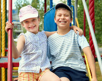 Enfant heureux sur le terrain de jeu extérieur, jeu en parc de ville, saison d'été, lumière du soleil lumineuse Photographie stock libre de droits
