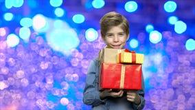 Enfant heureux tenant des boîte-cadeau de Noël clips vidéos