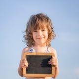 Enfant heureux tenant le tableau noir vide Image libre de droits