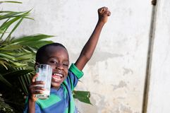 Enfant heureux tenant un verre de lait Photo stock
