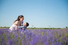 Enfant heureux tombant dans les bras de la mère de sourire sur le gisement de fleur Photographie stock