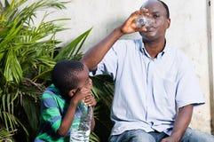 Enfant hors de l'eau à son père photographie stock