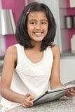 Enfant indien asiatique de fille à l'aide de l'ordinateur de tablette images stock