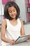 Enfant indien asiatique de fille à l'aide de l'ordinateur de tablette images libres de droits