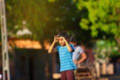 Enfant indien rural jouant le cricket photo stock
