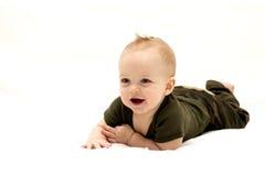 Enfant infantile de sourire se trouvant sur la couverture blanche Images libres de droits