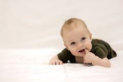 Enfant infantile de sourire se trouvant sur la couverture blanche Photo libre de droits