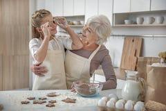 Enfant insouciant appréciant le procédé de boulangerie avec sa grand-mère Photographie stock