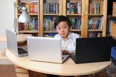 Enfant intelligent travaillant sur les ordinateurs multiples Photos stock