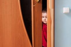 Enfant jetant un coup d'oeil par derrière la porte Photographie stock
