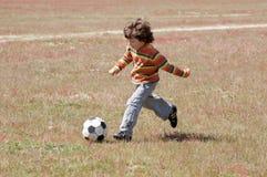 Enfant jouant au football Images stock