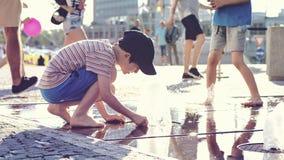 Enfant jouant avec de l'eau à la fontaine de rue Photographie stock