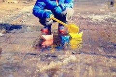 Enfant jouant avec de l'eau de papier bateaux au printemps photos libres de droits