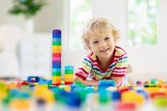 Enfant jouant avec des blocs de jouet Jouets pour des gosses photos stock