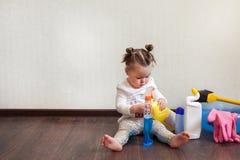 Enfant jouant avec des bouteilles avec des produits domestiques se reposant sur le plancher de la maison images stock