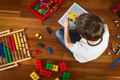 Enfant jouant avec des jouets tout en se reposant sur le plancher en bois Vue supérieure Photos stock