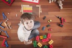 Enfant jouant avec des jouets tout en se reposant sur le plancher en bois dans sa chambre Vue supérieure Photos stock
