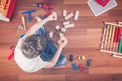 Enfant jouant avec des jouets tout en se reposant sur le plancher en bois dans sa chambre Vue supérieure Photographie stock libre de droits