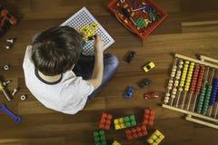 Enfant jouant avec des jouets tout en se reposant sur le plancher en bois Vue supérieure Photographie stock
