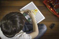 Enfant jouant avec des jouets tout en se reposant sur le plancher en bois Vue supérieure Photo stock