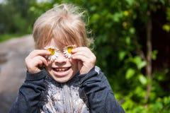 Enfant jouant avec des marguerites Photographie stock