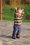 Enfant jouant avec la chaîne en acier Images stock