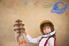 Enfant jouant avec la fusée de jouet de carton Images stock