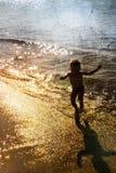 Enfant jouant avec la mer Photo stock