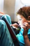 Enfant jouant avec la tablette Images stock