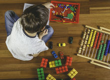 Enfant jouant avec la trousse à outils de jouets tout en se reposant sur le plancher dans sa chambre Vue supérieure Images libres de droits
