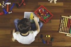 Enfant jouant avec la trousse à outils de jouets tout en se reposant sur le plancher dans sa chambre Vue supérieure Image libre de droits