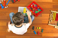 Enfant jouant avec la trousse à outils de jouets tout en se reposant sur le plancher dans sa chambre Vue supérieure Photo stock
