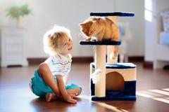 Enfant jouant avec le chat ? la maison Enfants et animaux familiers photo stock
