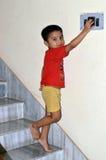 Enfant jouant avec le commutateur Photos libres de droits