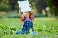 Enfant jouant avec le comprimé dehors Photographie stock