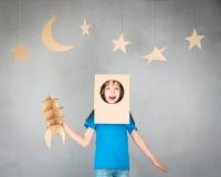 Enfant jouant avec le paquet de jet à la maison Images stock