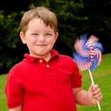 Enfant jouant avec le pinwheel d'indicateur américain Image stock