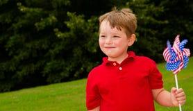 Enfant jouant avec le pinwheel d'indicateur américain Image libre de droits