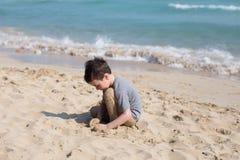 Enfant jouant avec le sable sur seule la plage Peu garçon près de mer Jeu d'été photo stock