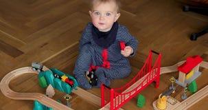 Enfant jouant avec le train en bois banque de vidéos