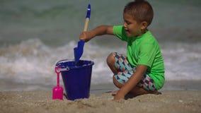 Enfant jouant avec une pelle dans le sable devant l'océan à la plage banque de vidéos
