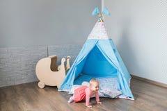 Enfant jouant avec une tente de tipi Images stock
